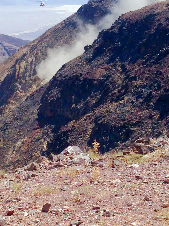 This photo provided by Panamint Springs Resort shows where a Navy fighter jet crashed Wednesday, July 31, 2019, in Death Valley National Park, injuring several people who were at a scenic overlook where aviation enthusiasts routinely watch military pilots speeding low through a chasm dubbed Star Wars Canyon, officials said. The crash sent dark smoke billowing in the air, said Aaron Cassell, who was working at his family's Panamint Springs Resort about 10 miles (16 kilometers) away. (Aaron Cassell/Panamint Springs Resort via AP)