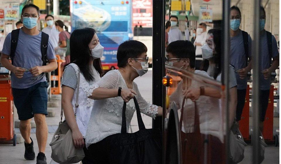Passengers in face masks board the bus at the Cross Harbour Tunnel Toll Plaza station in Hung Hom. Photo: Felix Wong