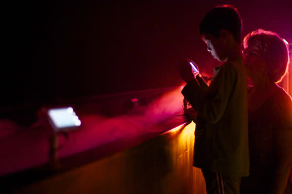 """A child uses a cell phone to see infrared """"lightning"""" in Dan Goods's """"Beneath the Surface"""" installation. The piece simulated the environment that the Juno spacecraft might go through as it explores the atmosphere of Jupiter."""