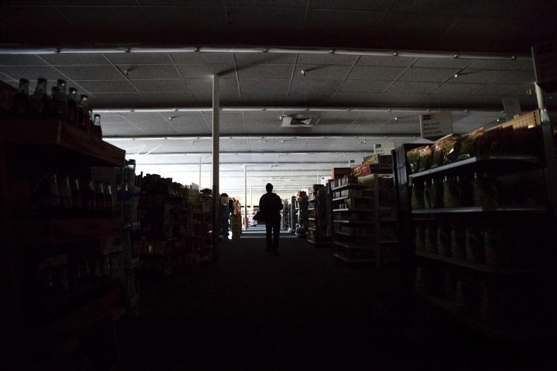 Shift supervisor James Quinn walks through a darkened CVS Pharmacy as downtown Sonoma, Calif., remains without power on Wednesday, Oct. 9, 2019. Pacific Gas and Electric has cut power to more than half a million customers in Northern California hoping to prevent wildfires during dry, windy weather throughout the region. (AP Photo/Noah Berger)