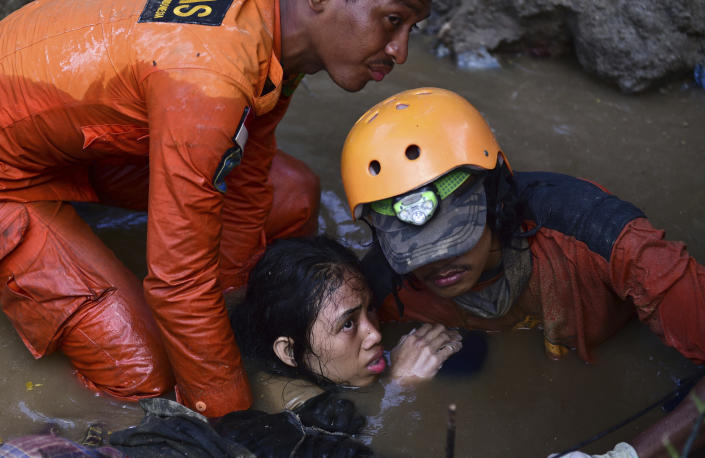 <p>Rescuers evacuate an earthquake survivor by a damaged house following earthquakes and tsunami in Palu, Central Sulawesi, Indonesia, Sunday, Sept. 30, 2018. Rescuers were scrambling Sunday to try to find trapped victims in collapsed buildings where voices could be heard screaming for help after a massive earthquake in Indonesia spawned a deadly tsunami two days ago. (Photo: Arimacs Wilander/AP) </p>