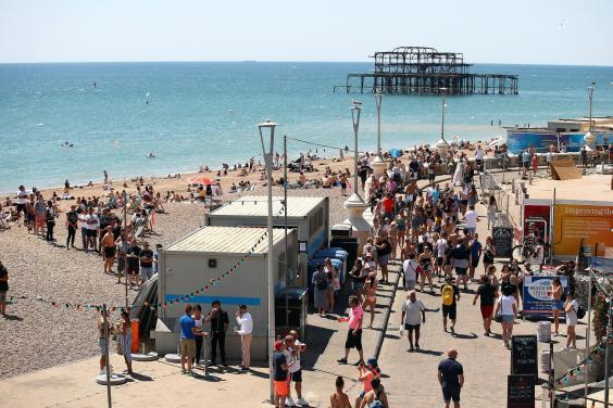 People queue for the toilet on Brighton Beach on 30 May (Bryn Lennon/Getty Images)