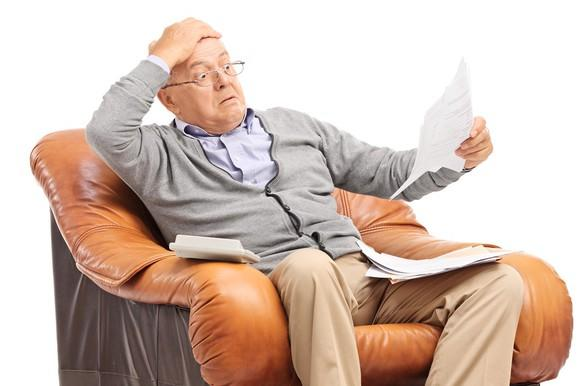 Older man sitting in a leather armchair looks at a paper with a shocked look on his face.
