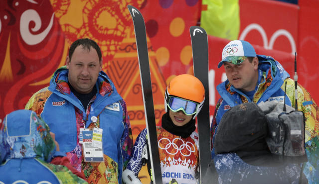Violinst Vanessa Mae starting under her father's name as Vanessa Vanakorn for Thailand, center, poses for a photograph with Olympic volunteers after competing in the first run of the women's giant slalom at the Sochi 2014 Winter Olympics, Tuesday, Feb. 18, 2014, in Krasnaya Polyana, Russia.(AP Photo/Gero Breloer)