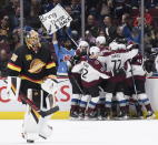 Colorado Avalanche's Nathan MacKinnon is mobbed by his teammates as they celebrate his overtime goal as Vancouver Canucks goalie Thatcher Demko skates off the ice after an NHL hockey game Saturday, Nov. 16, 2019, in Vancouver, British Columbia. (Darryl Dyck/The Canadian Press via AP)