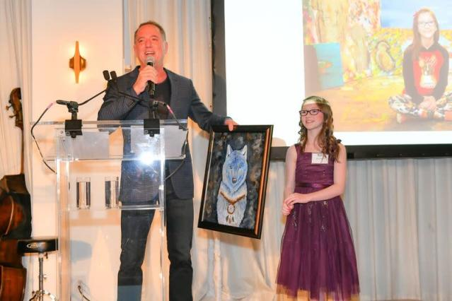 Jefferies CEO Rich Handler auctions off a painting from Bria Neff, an 11-year-old artist dedicated to saving endangered animals, during a fundraiser for the Wolf Conservation Center in New York.