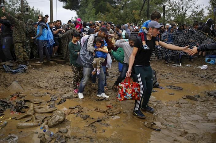 <p>Syrian refugees walk through the mud as they cross the border from Greece into Macedonia, near the Greek village of Idomeni, Sept. 10, 2015.<i> (Yannis Behrakis/Reuters)</i></p>