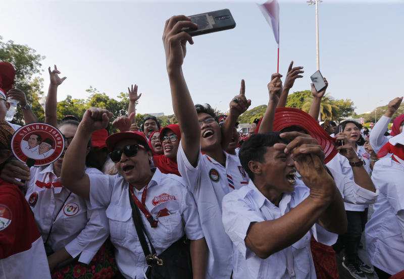 Supporters of Indonesian President Joko Widodo holds a large national Red-White flag during rally to celebrate his inauguration for his second term in Jakarta, Indonesia, Sunday, Oct. 20, 2019. Indonesian President Joko Widodo, who rose from poverty and pledged to champion democracy, fight entrenched corruption and modernise the world's most populous Muslim-majority nation, was sworn in Sunday for his second and final five-year term with a pledge to take bolder actions. (AP Photo/Tatan Syuflana)