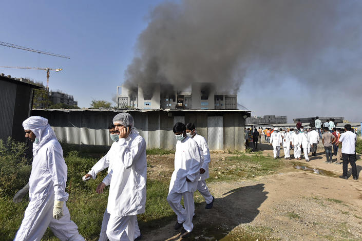 Workers wearing protective gear are seen after a fire broke out at the Serum Institute of India, in Pune, on January 21, 2021. / Credit: AFP via Getty