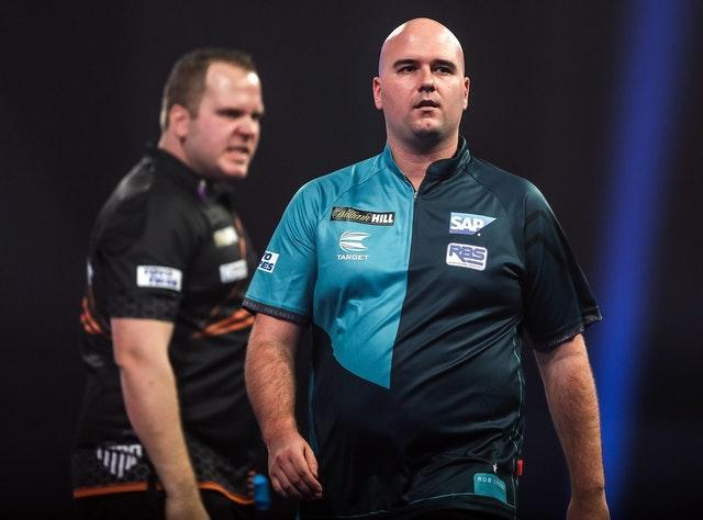 Rob Cross (right) walks off stage after losing to Dirk Van Duijvenbode (left) in the PDC World Championship at Alexandra Palace