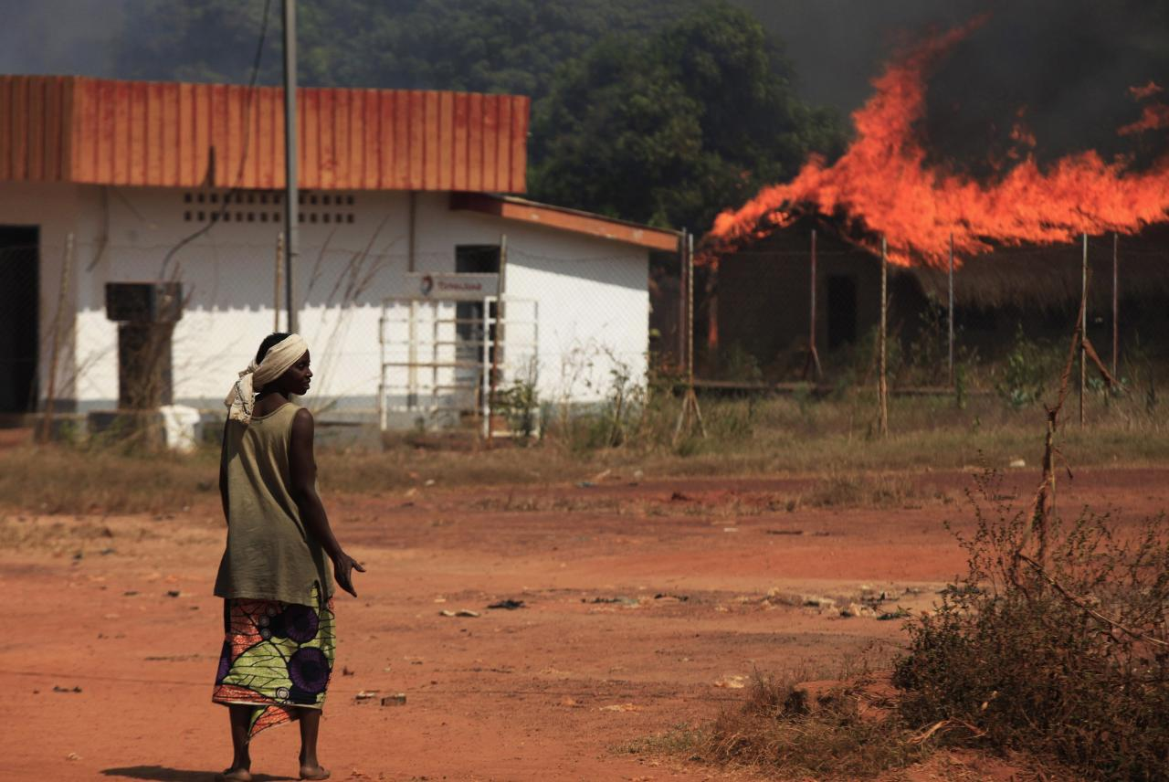 A woman looks at burning houses in Bossangoa, north of the capital Bangui January 2, 2014. Clashes between Muslims and Christians in Central African Republic's capital killed at least three on Wednesday as angry residents threw grenades and torched homes, witnesses said. REUTERS/Andreea Campeanu (CENTRAL AFRICAN REPUBLIC - Tags: CIVIL UNREST)