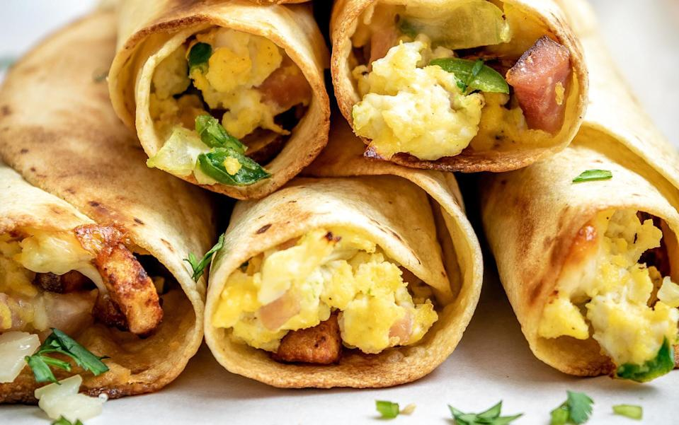 """<p>Start the day with all of your favorite breakfast ingredients wrapped in a tortilla. Lay out the fixings for the taquitos and have your kids roll them into the tortillas, then you can pop them into the oven.</p> <p><a href=""""https://www.thedailymeal.com/best-reviews/breakfast-taquitos?referrer=yahoo&category=beauty_food&include_utm=1&utm_medium=referral&utm_source=yahoo&utm_campaign=feed"""" rel=""""nofollow noopener"""" target=""""_blank"""" data-ylk=""""slk:For the Breakfast Taquitos recipe, click here."""" class=""""link rapid-noclick-resp"""">For the Breakfast Taquitos recipe, click here. </a></p>"""