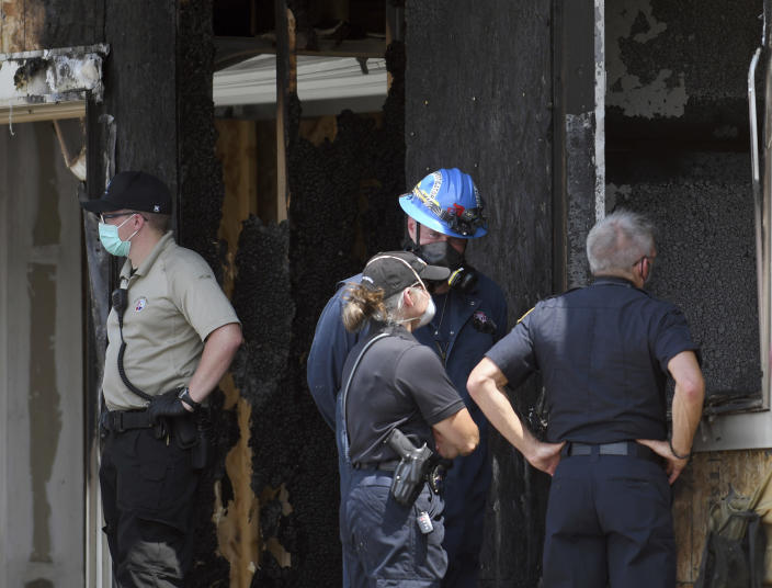 Investigators stand outside a house where five people were found dead after a fire in suburban Denver, Wednesday, Aug. 5, 2020. Three people escaped the fire by jumping from the home's second floor. Investigators believe the victims were a toddler, an older child and three adults. Authorities suspect was intentionally set. Witnesses told firefighters that three people on the second floor of the burning home jumped to safety. (AP Photo/Thomas Peipert)