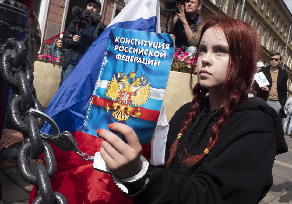 A woman handcuffs herself to a fence while holding a Constitution of the Russian Federation, during a rally supporting Khabarovsk region's governor Sergei Furgal in St.Petersburg, Russia, Saturday, Aug. 1, 2020. Thousands of demonstrators rallied Saturday in the Russian Far East city of Khabarovsk to protest the arrest of the regional governor, continuing a three-week wave of opposition that has challenged the Kremlin. (AP Photo/Dmitri Lovetsky)