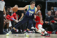 Dallas Mavericks forward Luka Doncic (77) drives the ball against Sacramento Kings guard Yogi Ferrell (3) in the second half of an NBA basketball game Sunday, Dec. 8, 2019, in Dallas. (AP Photo/Richard W. Rodriguez)