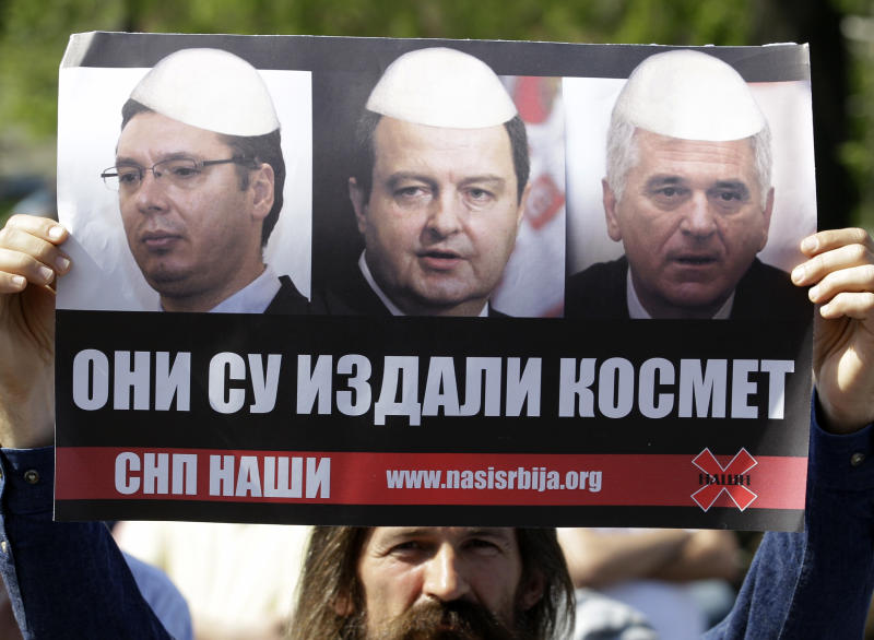 "A protester holds a poster depicting, from left: Serbian Progressive Party leader and deputy Prime Minister Aleksandar Vucic, Serbian Prime Minister Ivica Dacic and Serbia's President Tomislav Nikolic, that reads: ""They Betrayed Kosovo"" during a rally in front of Serbia's parliament building in Belgrade, Serbia, Friday, April 26, 2013. Serbian lawmakers are debating an EU-brokered deal on normalization of ties with breakaway Kosovo which was signed by the government and sets the former war foes on the path of reconciliation and EU integration. (AP Photo/Darko Vojinovic)"