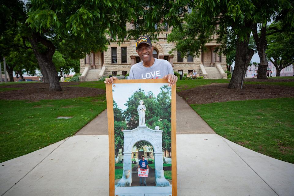 A man displays an image of himself protesting at the foot of a Confederate monument.