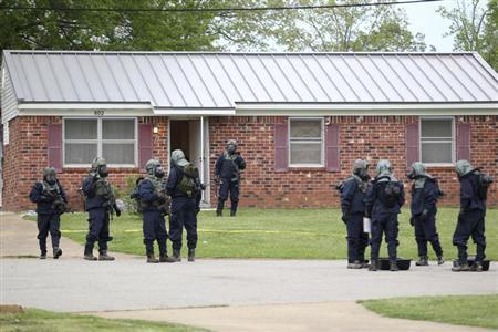 Federal officials stand outside the house of Paul Kevin Curtis while searching for evidence in Corinth