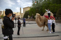 Tourists pose for photos with a camel outside the Id Kah Mosque in Kashgar in western China's Xinjiang Uyghur Autonomous Region, as seen during a government organized trip for foreign journalists, Monday, April 19, 2021. A human rights group is appealing to the United Nations to investigate allegations China's government is committing crimes against humanity in the Xinjiang region. Human Rights Watch cited reports of the mass detention of Muslims, a crackdown on religious practices and other measures against minorities in the northwestern region. (AP Photo/Mark Schiefelbein)