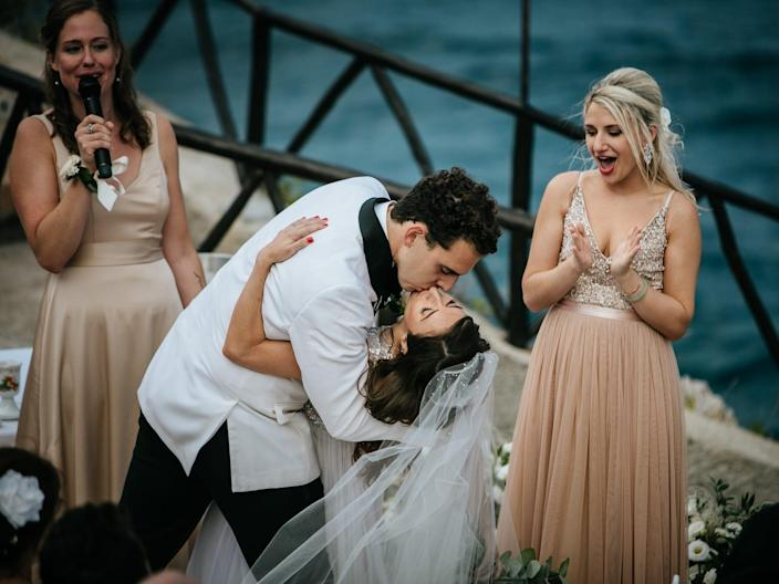 A groom dips and kisses a bride while two bridesmaids cheer.