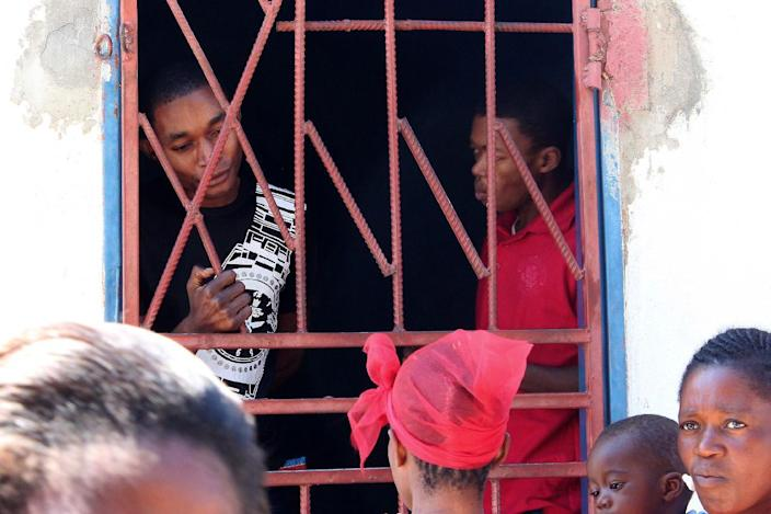 """Accused of having relations """"against the order of nature"""", James Mwape (R) and Philip Mubiana (L) are seen in a holding cell ahead of their trial at the Kapiri Mposhi magistrate court on July 3, 2014 (AFP Photo/)"""