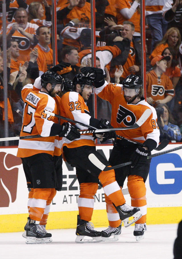 Philadelphia Flyers' Mark Streit, center, of Switzerland, celebrates his goal with Andrew MacDonald, left, and Jakub Voracek, right, of the Czech Republic, during the first period in Game 3 of an NHL hockey first-round playoff series against the New York Rangers, Tuesday, April 22, 2014, in Philadelphia. (AP Photo/Chris Szagola)
