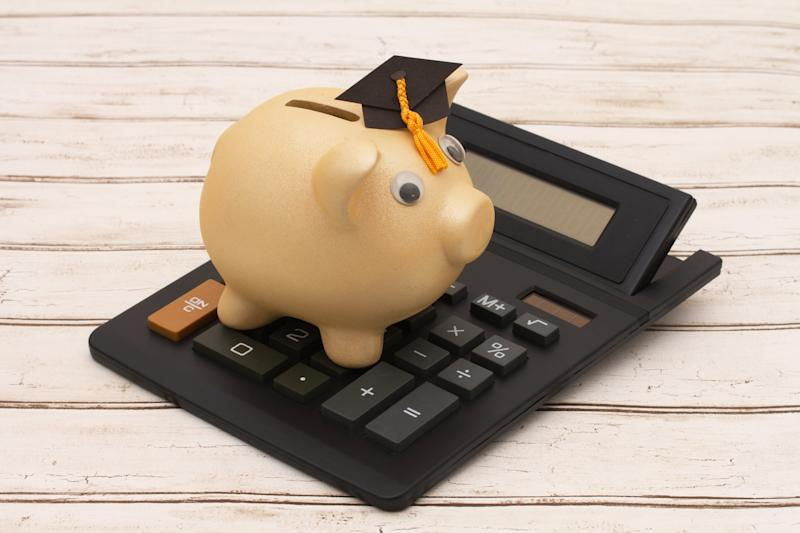 A piggy bank wearing a graduation cap sits on top of a calculator.