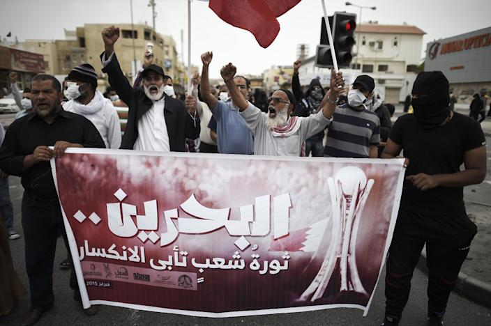 """Bahraini protesters hold a banner reading, """"Bahrain, a revolution of the people that refuse to be silent"""", during a demonstration to mark the fourth anniversary of the Arab Spring-inspired uprising on February 14, 2015, in the village of Daih (AFP Photo/Mohammed al-Shaikh)"""