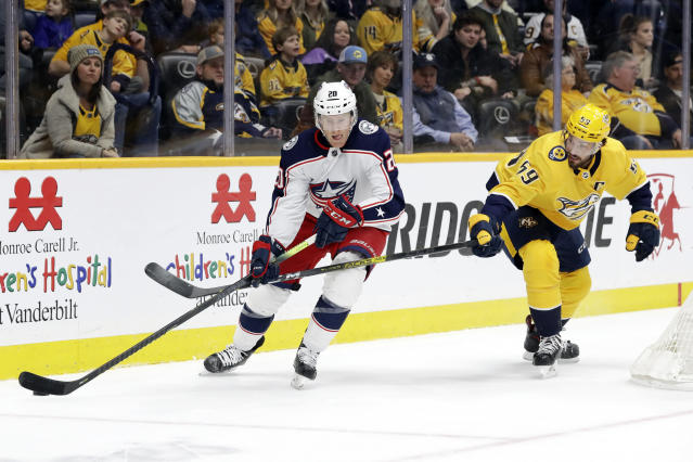 Columbus Blue Jackets center Riley Nash (20) is defended by Nashville Predators' Roman Josi (59), of Switzerland, in the first period of an NHL hockey game Saturday, Feb. 22, 2020, in Nashville, Tenn. (AP Photo/Mark Humphrey)