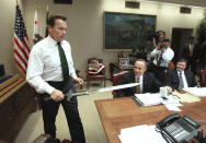 """FILE - In this Jan. 13, 2009 file photo, Gov. Arnold Schwarzenegger brings the sword he used in the movie """"Conan The Barbarian,"""" to the conference table before the start of budget negotiations with legislative leaders at the Capitol in Sacramento, Calif. Schwarzenegger, who came to office during California's historic 2003 recall election, will soon be releasing his autobiography, """"Total Recall: My Unbelievably True Life Story.""""(AP Photo/Rich Pedroncelli, file)"""