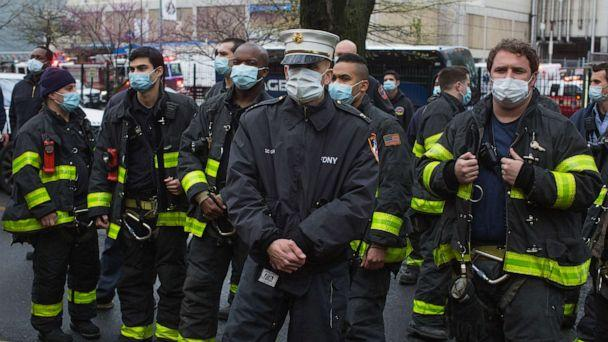 PHOTO: Firemen wearing protective masks watch the 7pm salute to healthcare workers amid the COVID-19 pandemic led by Mayor Bill De Blasio and his wife Charlene McCray on April 24, 2020 in Brooklyn, New York. (Andrew Lichtenstein/Corbis via Getty Images)