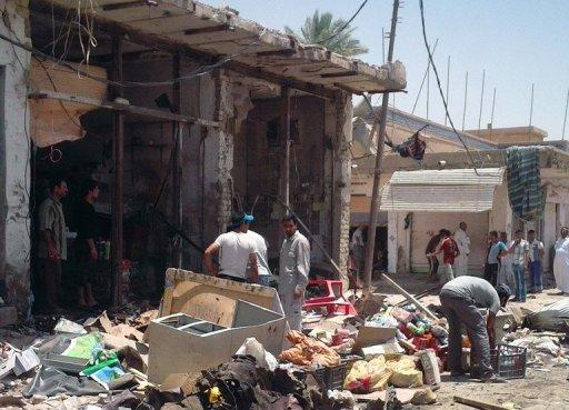 Iraqis inspect the damage following a car bombing in Zubaidiyah