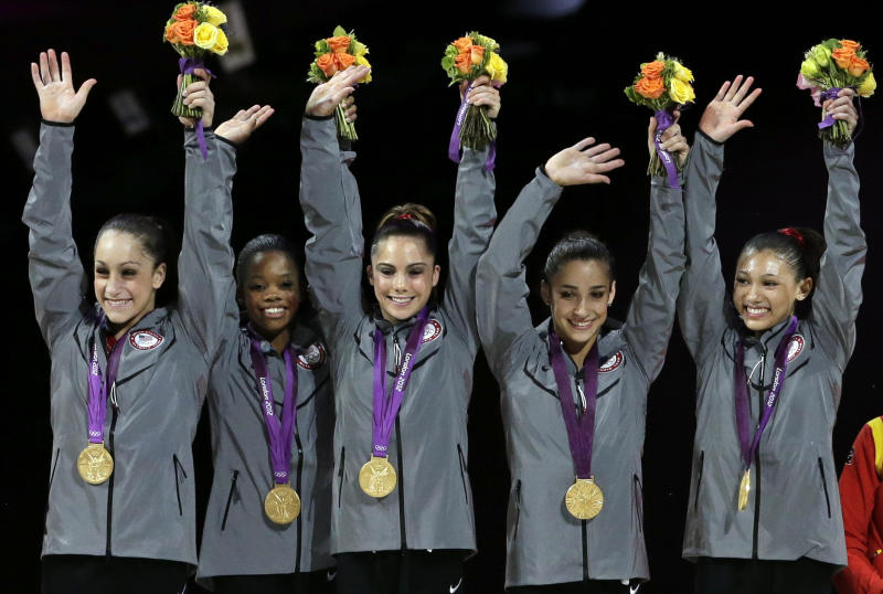 U.S. gymnasts, left to right, Jordyn Wieber, Gabrielle Douglas, McKayla Maroney, Alexandra Raisman, Kyla Ross raise their hands on the podium during the medal ceremony during the Artistic Gymnastic women's team final at the 2012 Summer Olympics, Tuesday, July 31, 2012, in London. Team U.S. won the gold. (AP Photo/Gregory Bull)