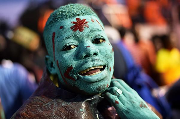 """A reveler with body painted with a mixture of cane sugar and coal, performs during the 2017 National Carnival Parade on February 26, 2017, in the city of Les Cayes, southwest Haiti. The name of the carnival for this year is """"Tet ansanb pou gran sid leve kanpe"""", in Haitian creole, (together for the South to rise up)."""