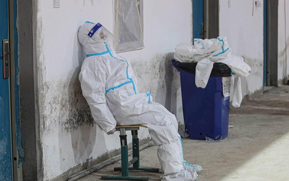 A medical worker wearing a protective suit has a rest at a temporary COVID-19 testing center on January 5, 2021 in Shenyang
