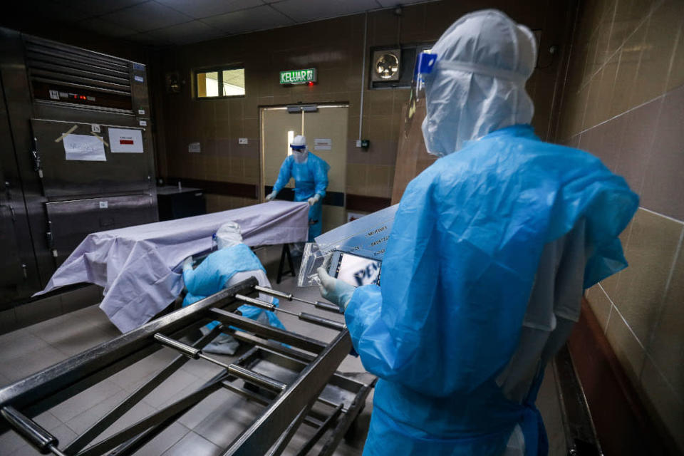 Forensics personnel prepare the body of a recently deceased Covid-19 patient for identification before burial at the Penang General Hospital, August 24, 2021. — Picture by Sayuti Zainudin