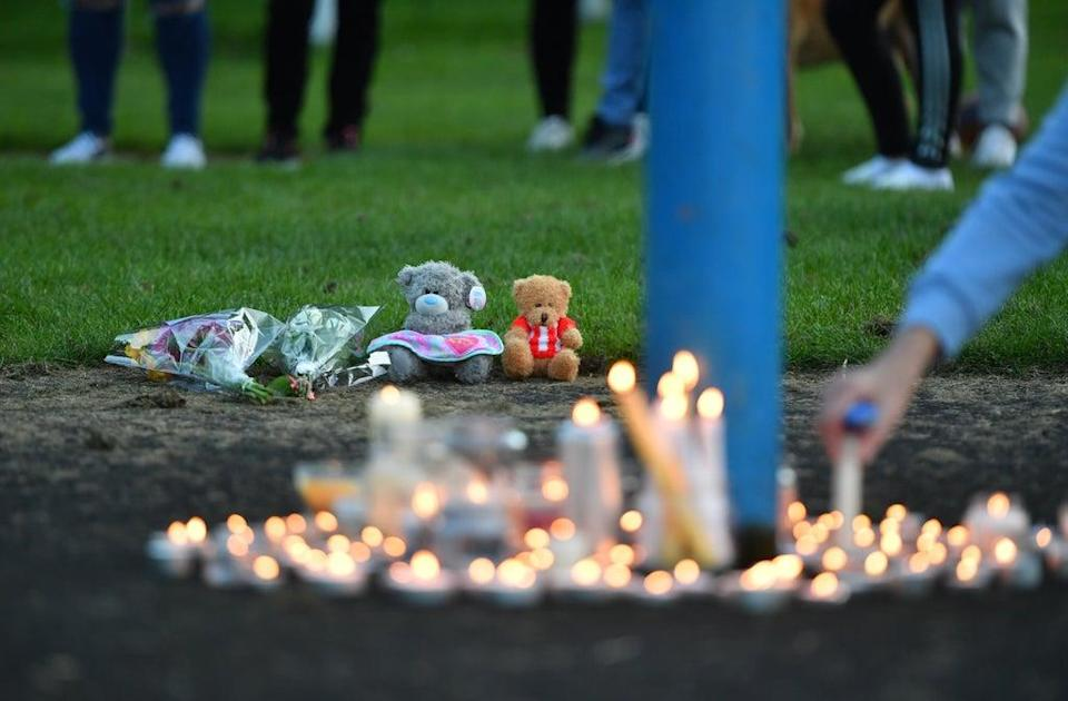 Flowers, soft toys and candles are seen at a vigil at the scene (Anthony Delvin/PA) (PA Wire)