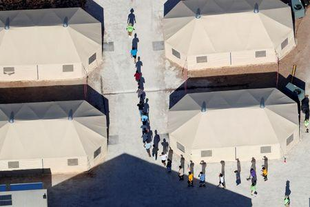 Immigrant children walk in single file between tents in their compound next to the Mexican border in Tornillo, Texas