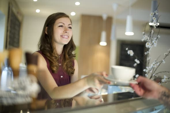 young woman working in a coffee shop hands over the cup