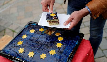 FILE PHOTO: Arne Lietz, candidate of the Social Democratic Party (SPD) for the upcoming European Parliament elections serves a piece of cake as he campaigns in Quedlinburg, Germany, May 4, 2019. Picture taken  May 4, 2019.    REUTERS/Fabrizio Bensch/File Photo