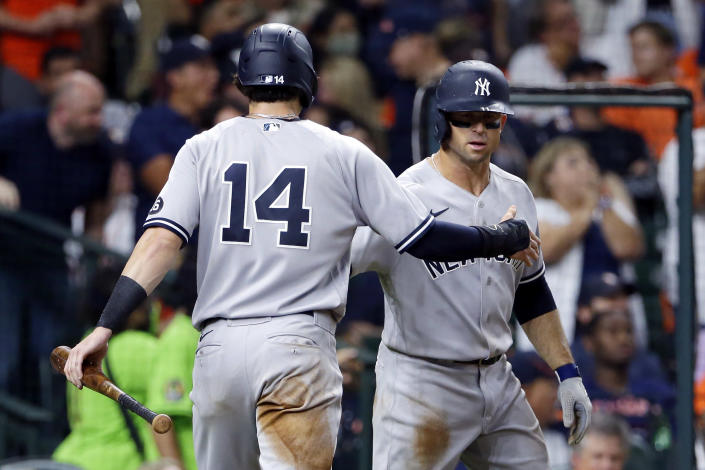 New York Yankees' Tyler Wade (14) and Brett Gardner, right, celebrate after both scored on a double by DJ LeMahieu during the seventh inning of the team's baseball game against the Houston Astros on Friday, July 9, 2021, in Houston. (AP Photo/Michael Wyke)