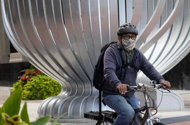 A cyclist wearing a mask bikes past the Stanley Cup statue on Sparks Street earlier this week. (Trevor Pritchard/CBC - image credit)