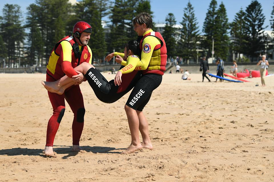 Volunteer Surf Life savers perform a rescue drill during a Surf Life Saving season launch at Manly Beach in Sydney.