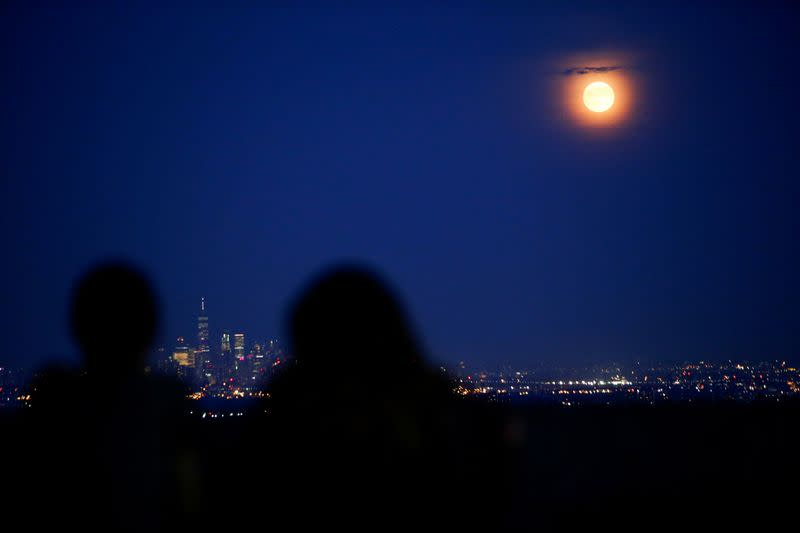 FILE PHOTO: People watch the full moon while it rises over the skyline of New York and One World Trade Center as seen from West Orange in New Jersey