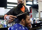 Mike Brown, pictured cutting the hair of Kendrick Furbush at The Shop Hair Spa in Hyattsville, Maryland on February 25, 2021, says he isn't shocked by skepticism about vaccines