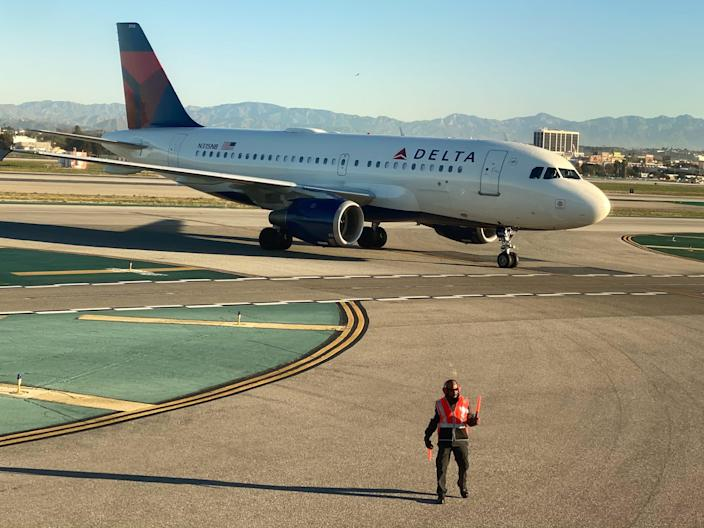 An airport worker guides a Delta Air Lines Airbus A319 plane on the tarmac at LAX in Los Angeles