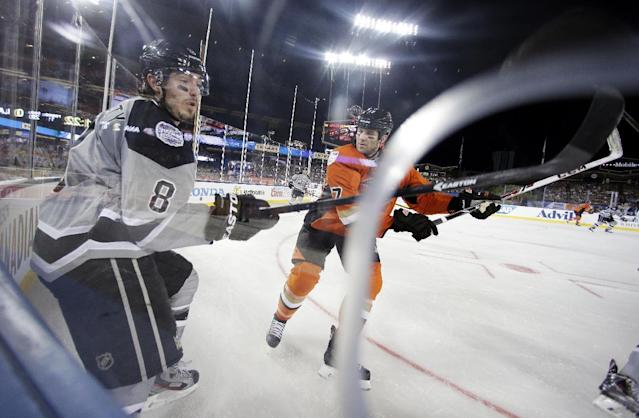 Los Angeles Kings defenseman Drew Doughty, left, and Anaheim Ducks left wing Dustin Penner battle for the puck during the first period of an NHL outdoor hockey game at Dodger Stadium in Los Angeles, Saturday, Jan. 25, 2014. (AP Photo/Chris Carlson)