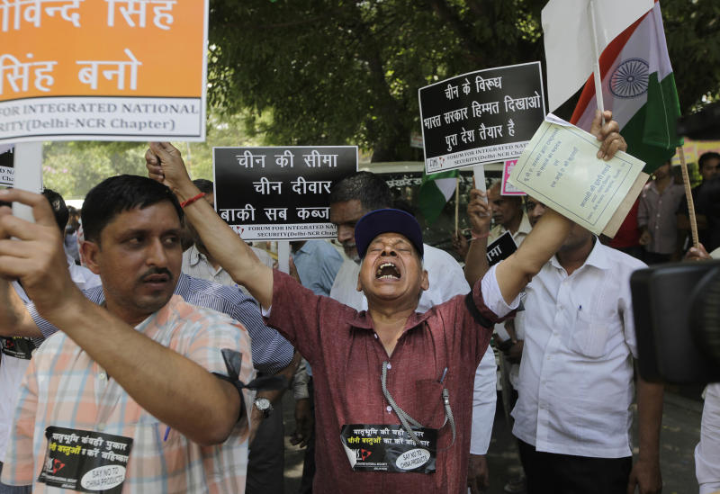 """Indian protesters shout slogans against the alleged incursion by Chinese troops into Indian territory, during a protest in New Delhi, India, Wednesday, May 1, 2013. India says Chinese troops crossed the de facto border between the countries and went 10 kilometers (six miles) into Indian territory on April 15. About 50 Chinese soldiers pitched tents and are camping in Daulat Beg Oldi in the Ladakh region of eastern Kashmir. The placard at right in Hindi reads: """"Show some courage against China, the whole country is ready."""" (AP Photo /Manish Swarup)"""