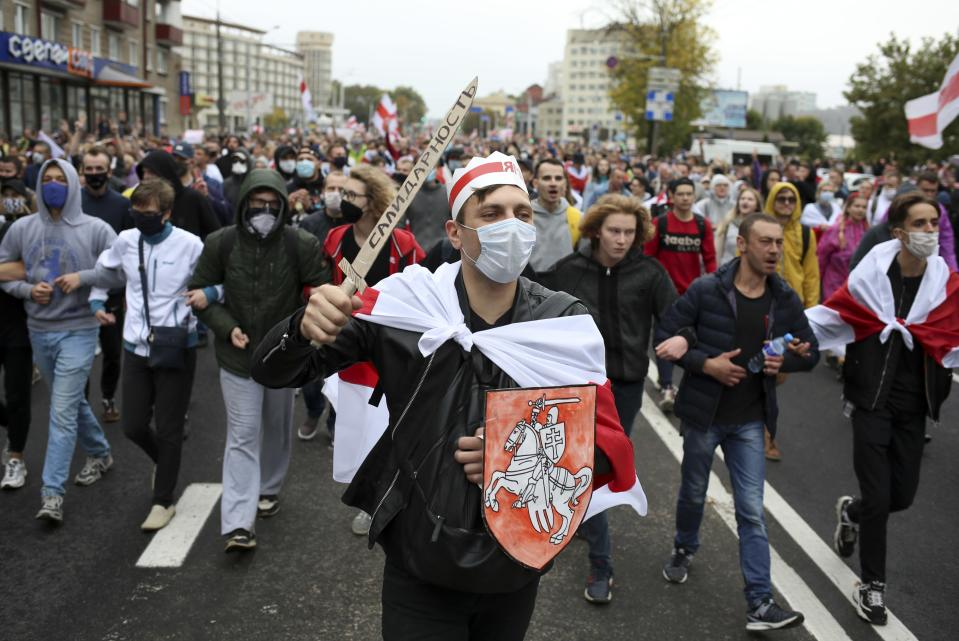 "Demonstrators, one of them wearing an old Belarusian nation flag and holding a cardboard sword reading ""solidarity"" march during an opposition rally to protest the official presidential election results in Minsk, Belarus, Sunday, Sept. 27, 2020. Hundreds of thousands of Belarusians have been protesting daily since the Aug. 9 presidential election. (AP Photo/TUT.by)"