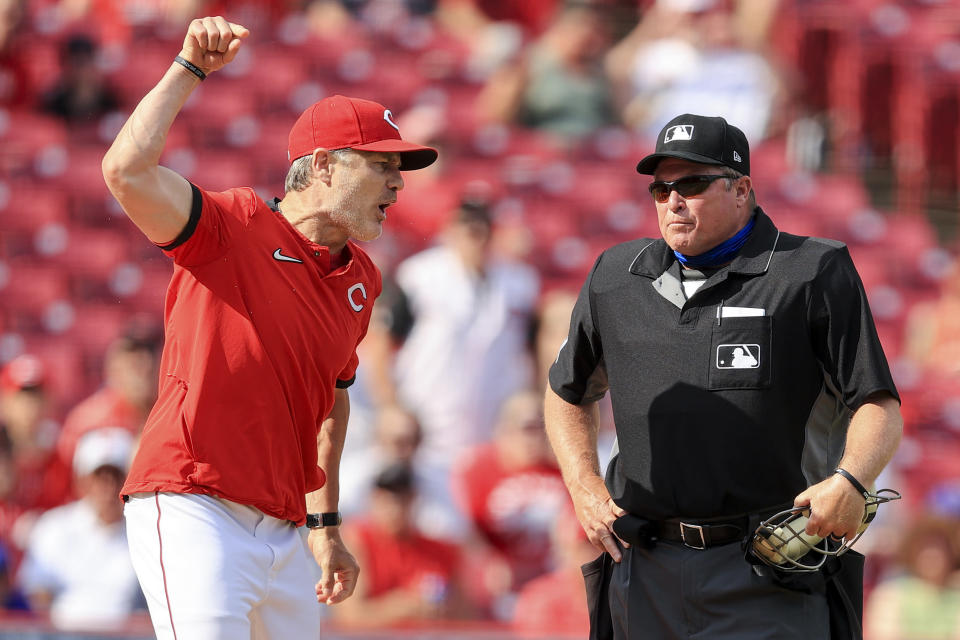 Cincinnati Reds' David Bell, left, reacts after being ejected from a baseball game by MLB umpire Marvin Hudson, right, during the fifth inning against the Colorado Rockies in Cincinnati, Saturday, June 12, 2021. (AP Photo/Aaron Doster)